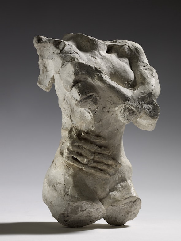 A plaster sculpture of a female torso with a skeleton hand resting on her stomach.
