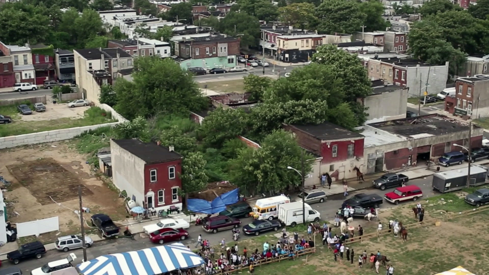 An aerial view of the Horse Day event shows rundown row houses and empty lots, illustrating the area's poverty.