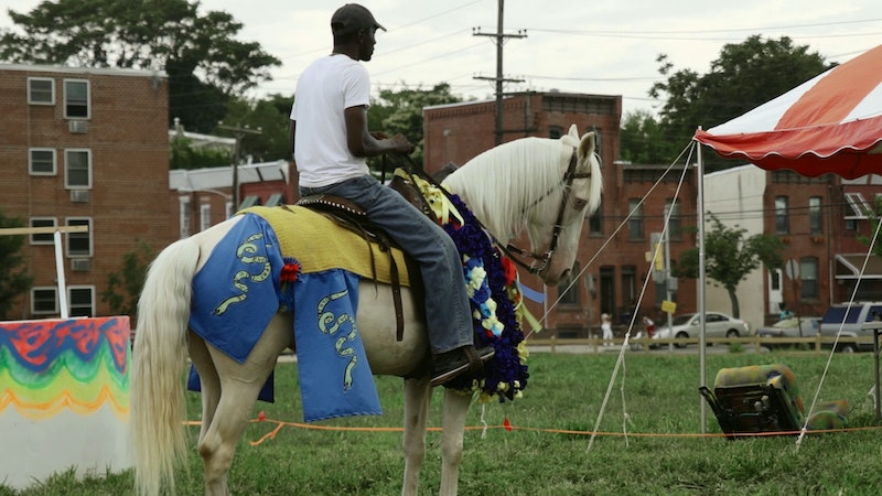 A rider sits atop a brightly costumed horse.