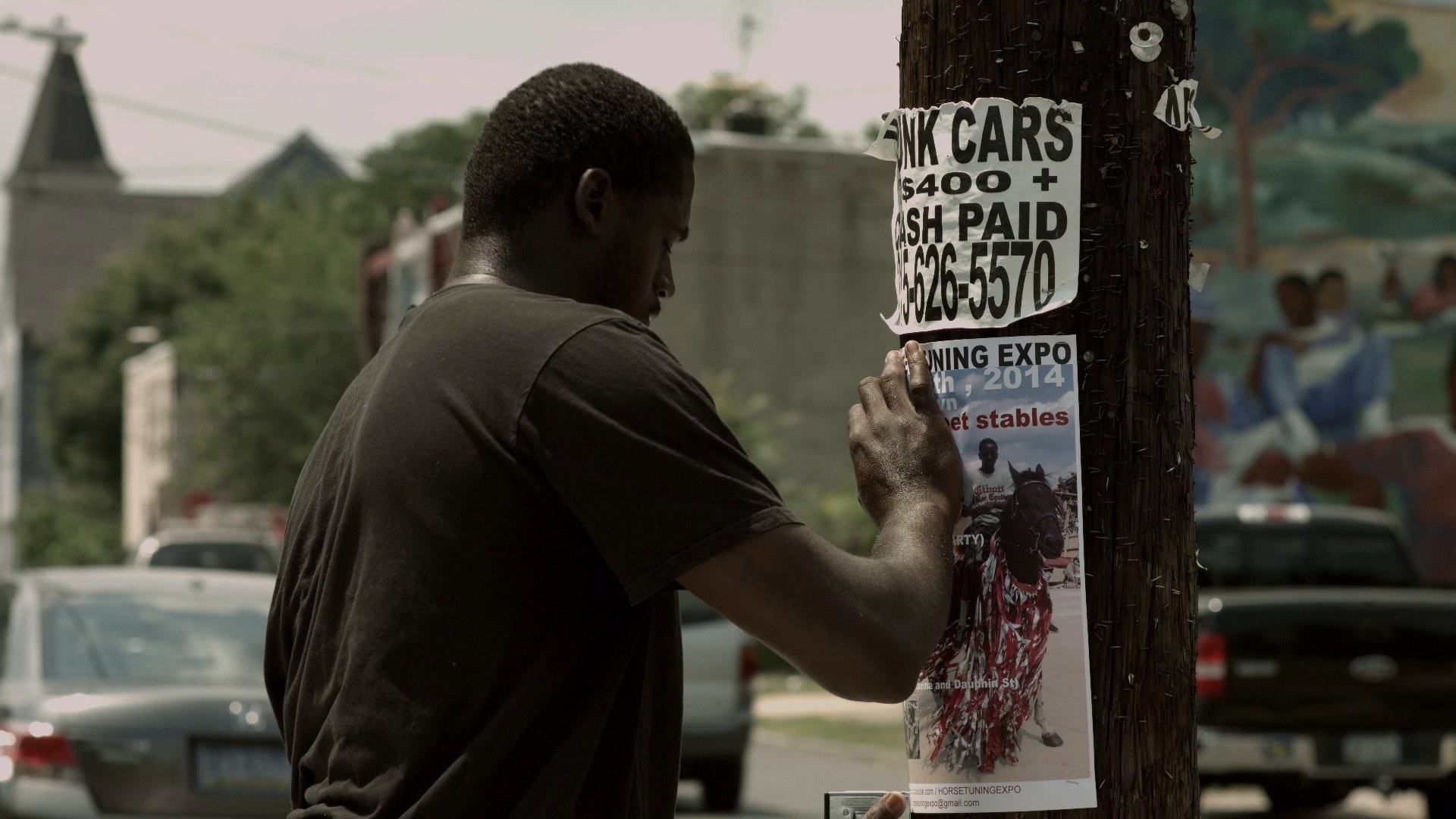 A rider pins a poster for the Horse Day event to a utility pole.