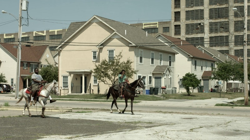 Two men ride horses through a poor area of the city.