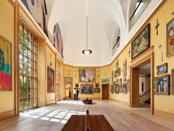 A bright gallery inside the Barnes Foundation is hung with salon-style displays of paintings.