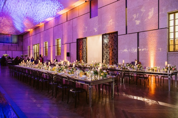 Rows of dinner tables line the court, topped with festive flowers.