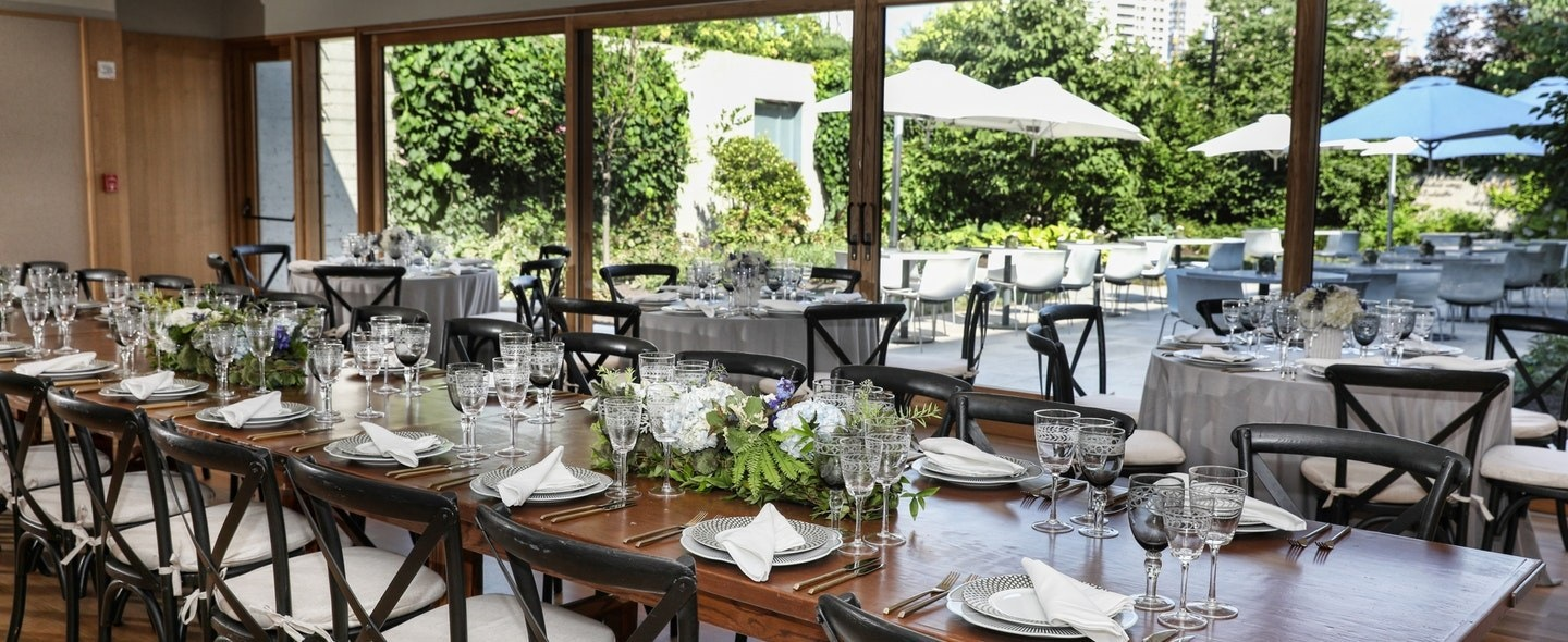 In the Garden Pavilion, tables set with china and wine glasses overlook a garden.