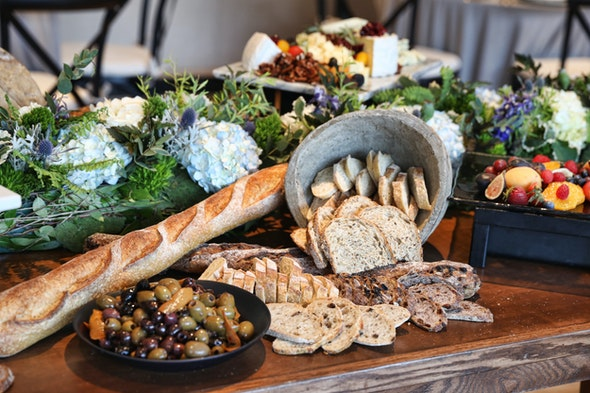 A table is topped with an attractive array of bread, olives, and fruit.