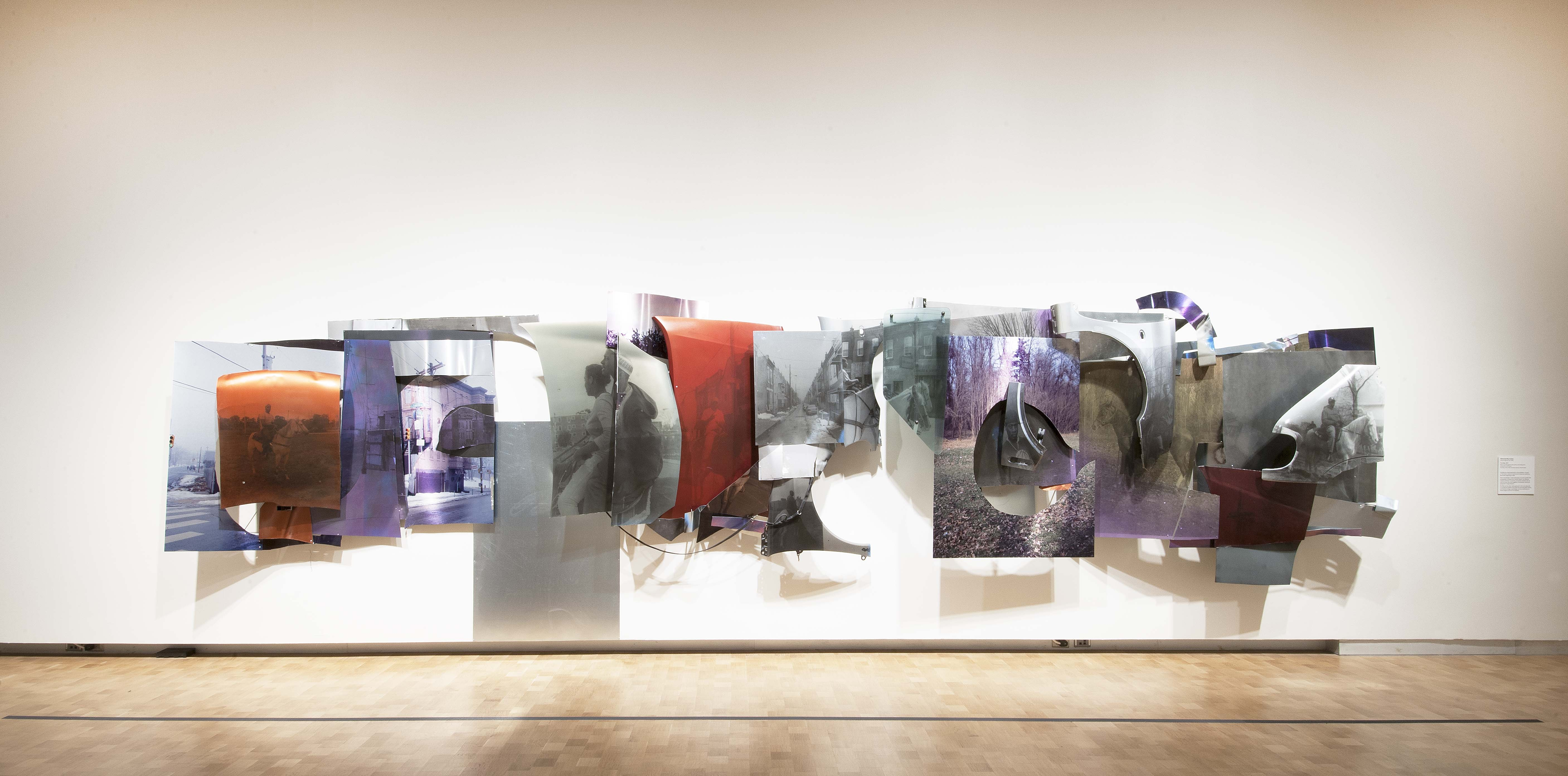 A long construction of metal car parts printed with images from Horse Day is hung in the exhibition.