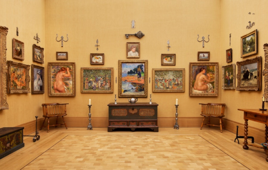 A mix of paintings, metalwork, and decorative objects cover the walls of a gallery space.